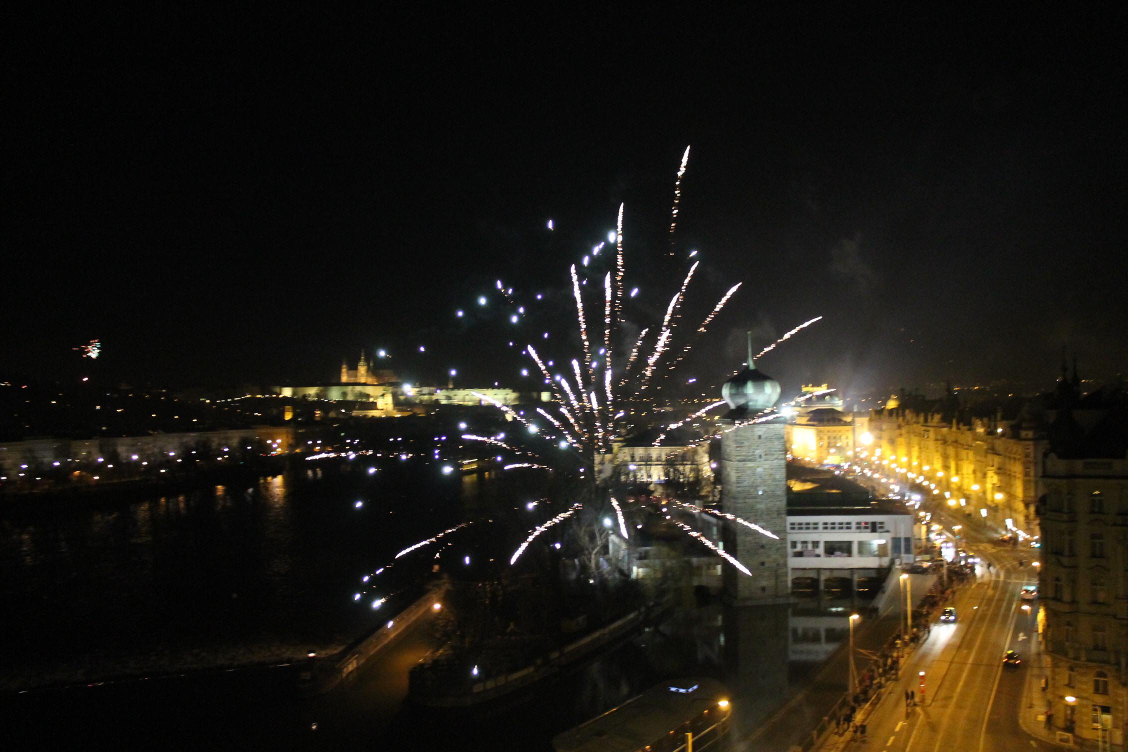 Prague : Le château illuminé et un feu d'artifice par dessus les toits